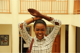 Excited Haitian woman holds a eNABLE hand above her head.
