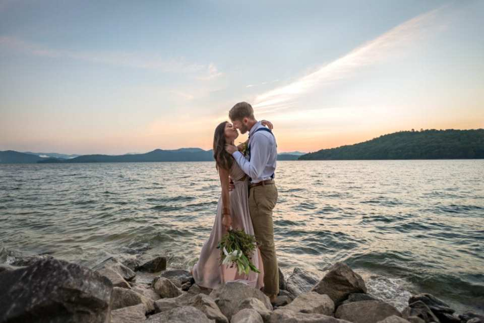 An couple kissing on the rocky shoreline before a lakeside elopoement ceremony in South Carolina