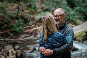 A couple snuggles with big smiles while standing in the creek deep in Pisgah National Forest. The rocky creek is surrounded by lush greenery