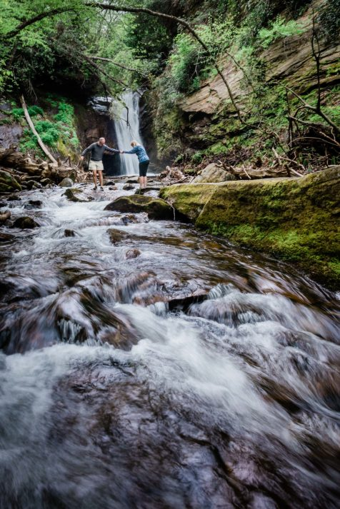 A couple explores a waterfall as a site for their elopement in Pisgah National Forest. Stream pours over mossy rocks, as the man offers a hand to the woman as she steps across the stream. A waterfall crashes directly behind them.