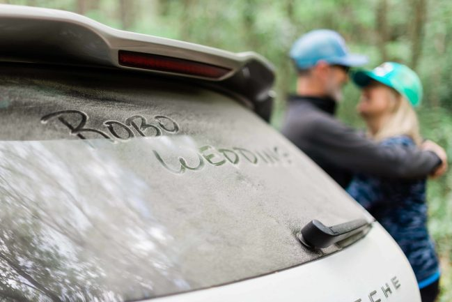 """A couple snuggles in the background with trees behind them, while their car is dusty from driving on the forest service dirt roads has """"RoBo Wedding"""" scrawled in the dirt on the back window"""