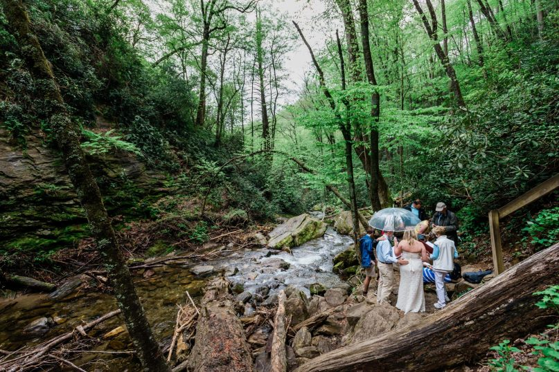 A couple and their family take part in an adventure elopement ceremony in a forest hollow overlooking a rock filled stream that feeds from the rushing waterfall that is just outside of the frame. The bride, groom and their families stands in a tight circle as they read elopement vows and the officiant performs the ceremony.