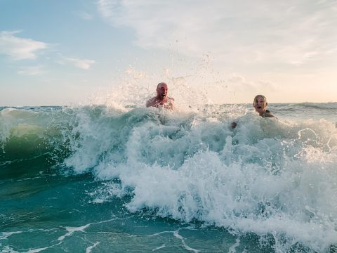 A couple playing and laughing as a wave hits them in the ocean by Charleston Elopement Photographer