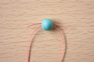 2.Take another 8mm bead, hold it so the hole is horizontal and take one thread through left to right, and the other right to left. This is called a crossover bead.