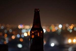 Bottle of home brewed beer city lights behind