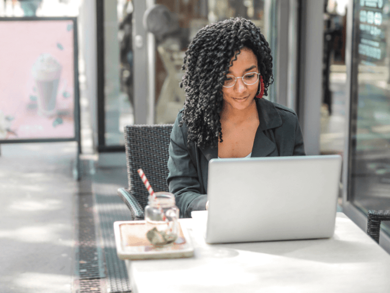 Photo of woman sitting outside at a cafe, looking at her laptop screen