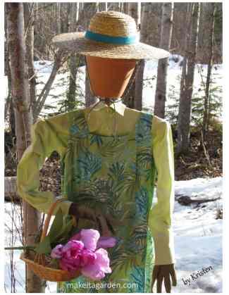 Un épouvantail habillé en femme dans une longue robe d'été et un chapeau de paille. Elle tient un panier de bulbes de tulipes