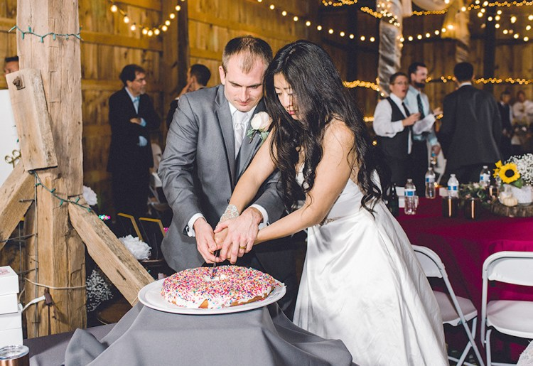 Bride and groom cutting a giant frosted doughnut with both hands