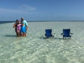 Family with chairs at the sandbar