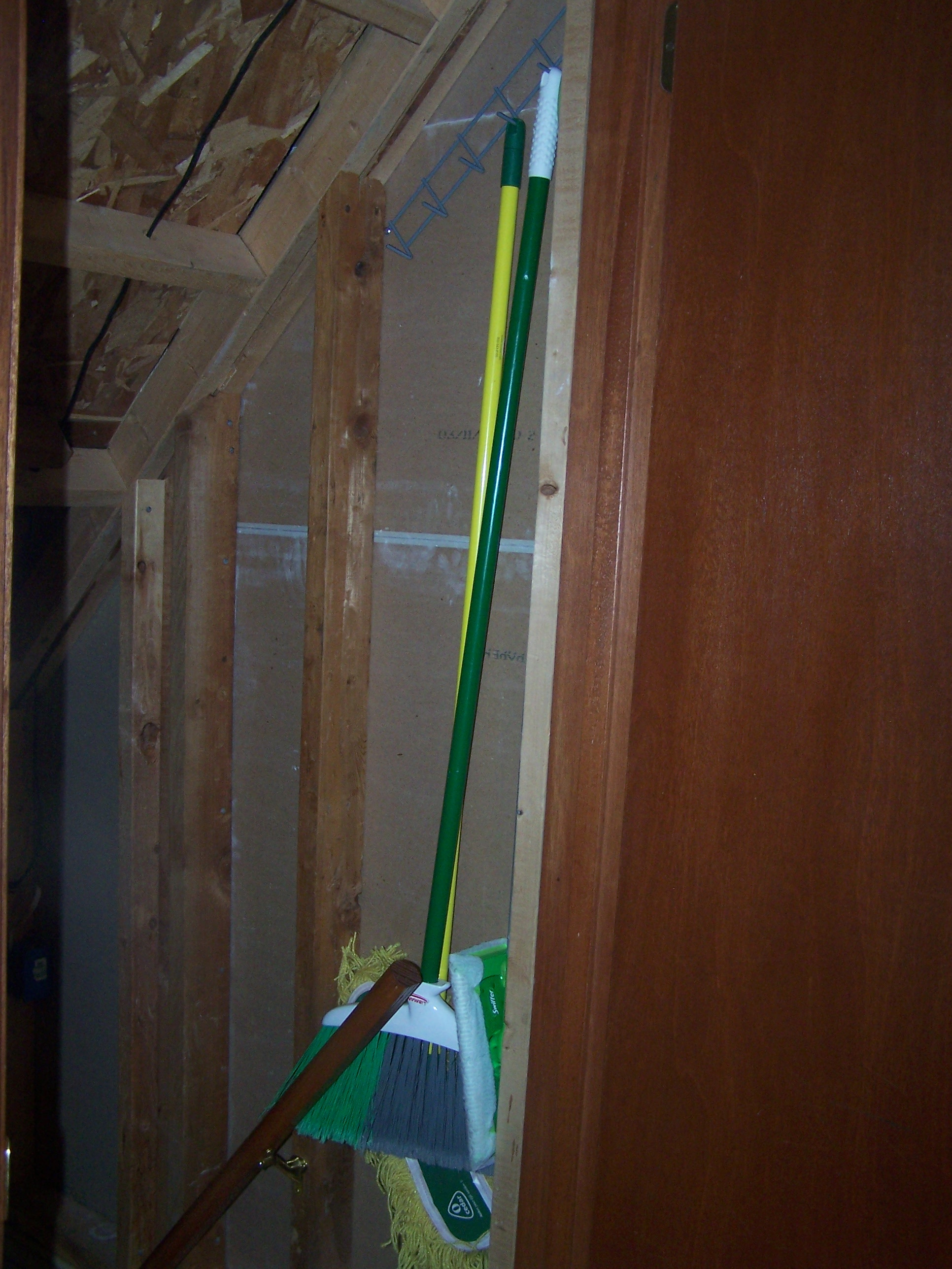 The brooms and mops hanging so nicely just inside our basement door.
