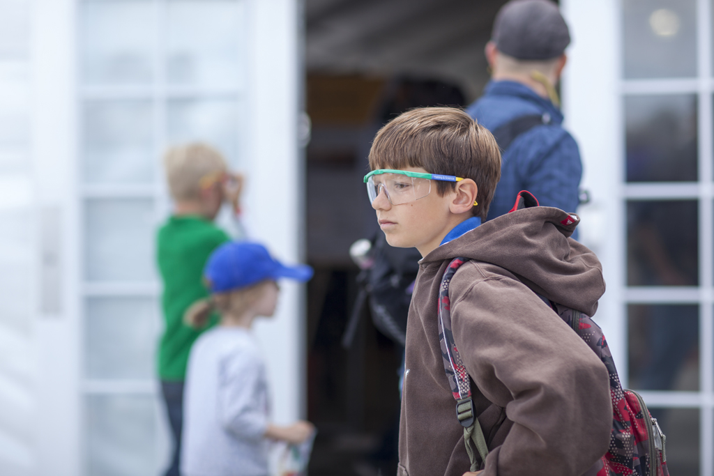 SAN MATEO, CA May 20 2016 - A student wearing safety glasses waits for his companions prior to entering the Young Makers activity center at the 11th Annual Maker Faire Bay Area at the San Mateo County Event Center.