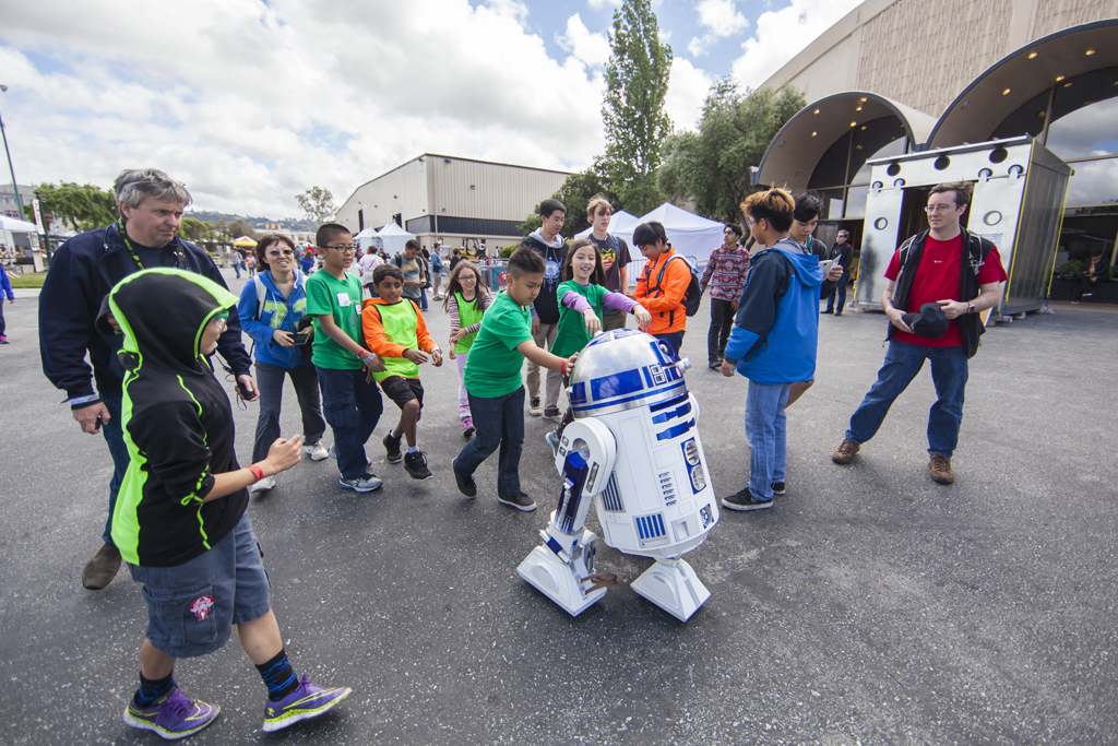 SAN MATEO, CA May 20 2016 - A group of children follow R2D2 as he rolls through the 11th Annual Maker Faire Bay Area at the San Mateo County Event Center.