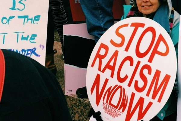 """Person holding a sign which reads, """"Stop Racism Now."""""""