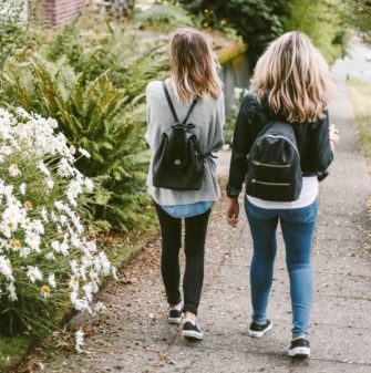 Two young blondes walking with backpacks.