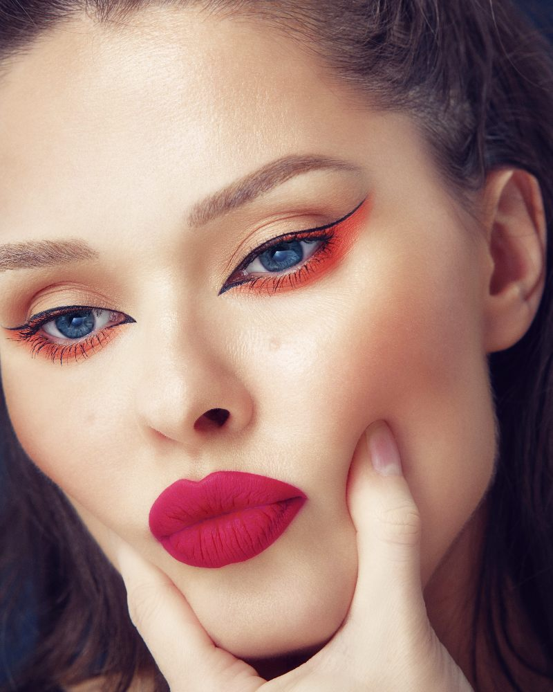 beautiful brunette girl neon graphic eyeliner makeup and hot red pink lips pouting   graphic liner set