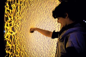 jumbled squiggles of yellow light cover a flexible membrane as a person pushes their fist into the center