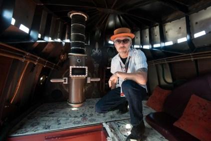 Lead artist of Five Ton Crane's Nautilus submarine art car, Sean Orlando, poses within its handmade interior.