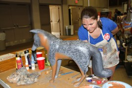 Jaclyn Bowen paints one of the many carved wooden characters that will be part of the working carousel operating in Kingsport starting next spring.