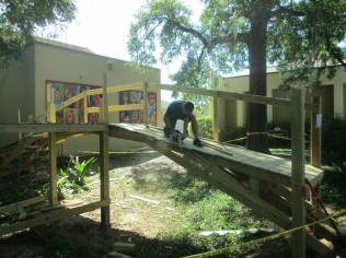 """A student cuts the edges with a circular saw. """"It was very satisfying to teach these kids, many of whom never touch a power tool, to do this kind of work,"""" said Robert."""