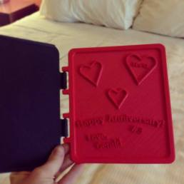 """Here's a gift/project idea from MAKE reader Gerald Beranek: """"Instead of the traditional Hallmark card and flowers, I decided to design and 3D print my own opening/closing/latching card for my wife on our 3 year wedding anniversary. I printed the base in red and the cove in black. I used my Makerbot Rep2 to do the printing.It was a fun little project and my wife and her family and friends loved it!She hands the 3D printed card around at all our family functions and you wouldn't imagine the amusement about it! It is all because everyone knows I am a true maker at heart, but no one ever thought a card could be 3D printed(some friends and family still can't imagine 3D printing!). Check out his 3D printing facebook page: www.facebook.com/generationyworx"""
