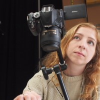 A cheap tripod is better than no tripod; for years I used a $15 Sunpak with no complaints. Some fancier models cantilever over your bench, or if your bench is sturdy you can use a clamp-on articulated arm, like my Manfrotto Magic Arm and Super Clamp.