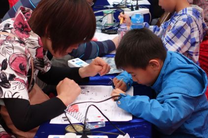 An intent young boy works on soldering.