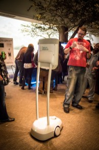 A guest gives a thumbs up to a woman attending the event via telepresence using Beam.