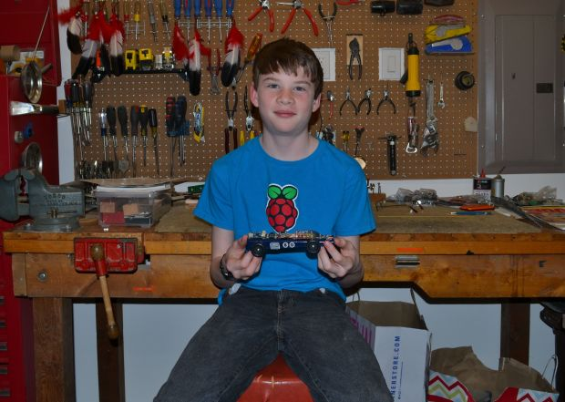 Figure 1. A boy and his Arduino-powered Pinewood Derby car.