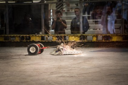 Sparks fly when a sledgehammer slam bot goes up against a well shielded wedge bot.