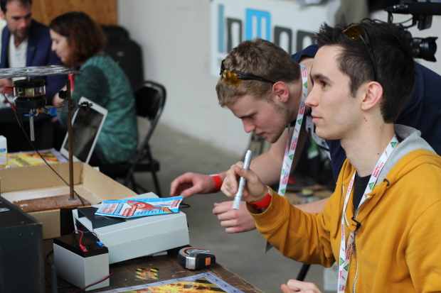 YouTube creator Experiment Boy signs posters for his fans while showing off his builds at the Maker Faire in Saint Malo.