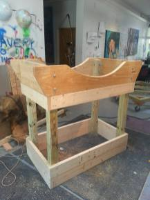 """Next it was time to build the drum stand. We used two 2x12s (which we shaped into the cradle), 4x4s for the legs, and 2x6s for additional strength. All was held together with ½"""" carriage bolts and lock washers."""