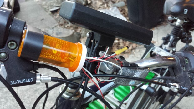The PSoC 4 BLE module encased inside a pill container, mounted to the handlebars.