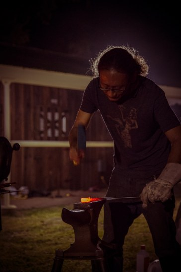 A blacksmith works on his project during Open Forge.