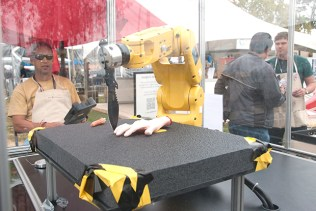 A robot arm aces the old knife-between-the-fingers trick at Google's Making Science exhibit.