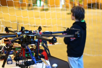 A young maker looks out over the fly-zone of the Drone Area at Maker Faire Paris.