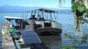 Solar pontoon boat in the foreground, with the house boat in the background.