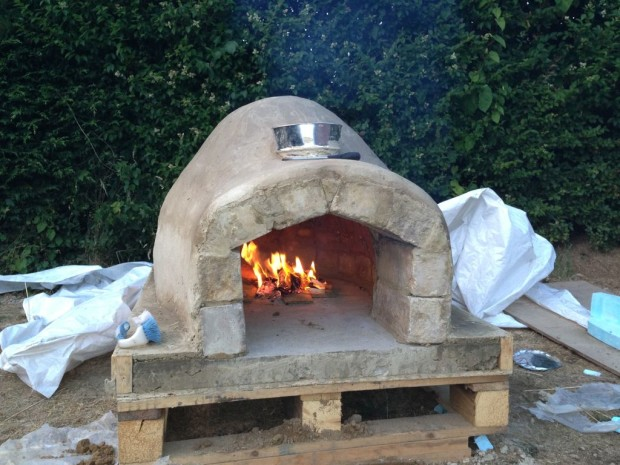 """For this build, the creators used bricks, cement, a few other materials,  and, uniquely, a wood pallet. As the author puts it, """"it always ends up  getting lit ... - Pick Your Pizza: 6 Outdoor Ovens You Can Build Make:"""