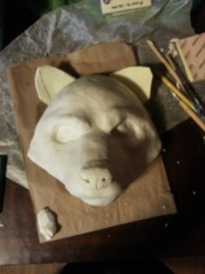Using the plaster face cast as a base, Borchardt begins sculpting the character.