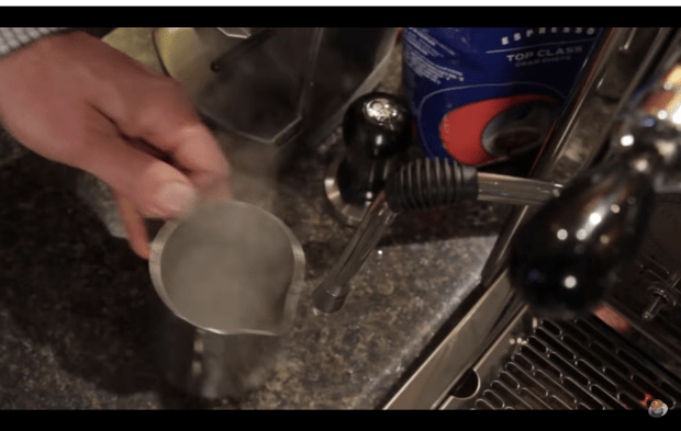 Todd from Whole Latte Love uses an empty pitcher to contain the vapor as he pulses the wand before use. Screenshot from How to Create Latte Art