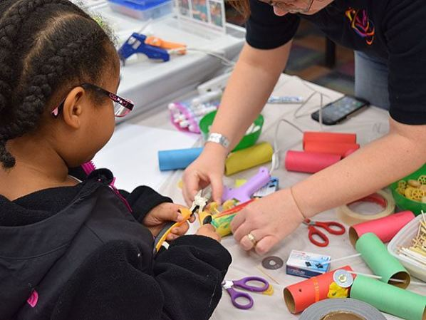 A young attendee learns to use clippers as she builds a miniature car for a Nerdy Derby. Photo credit: Doug Baldwin
