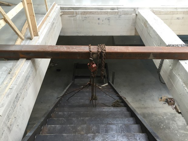 View of stair from above with temporary beam and chain hoist they used to haull it into place. Photo by Will Holman