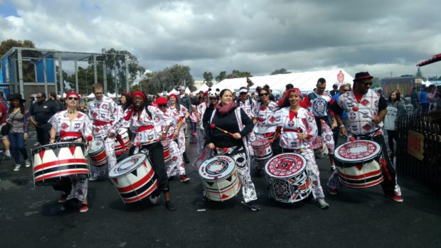 A drum line rolls through Zone 5 into the heart of the Faire. (10:50am Sophia Smith)