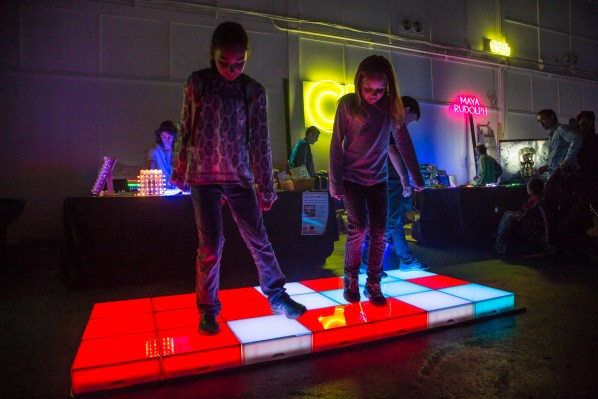 Two young girls playing on a light up square floor.