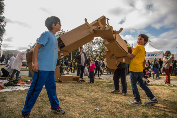 Two young boys mock fight using oversized cardboard robot arms.