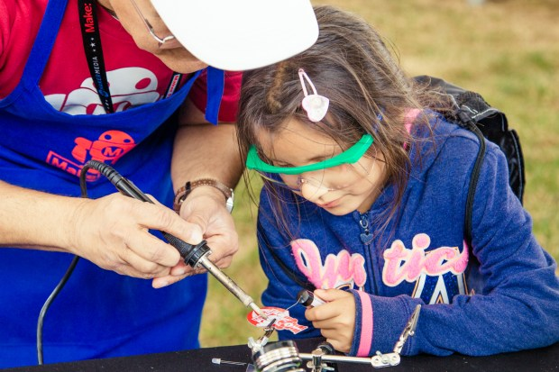 A middle aged woman holds a soldering iron for a young girl holding the wire to help solder a pin.