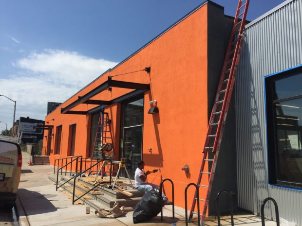 Orange paint is up on the east facade, as well as steel canopies over the doors. Image by Will Holman