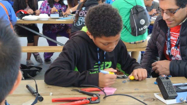 Soldering circuits at Maker Camp Live.
