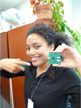 """Jendai shows off a radio frequency amplifier board that she put together, she explains, """"for a miniaturized laser heterodyne radiometer (mini-LHR). Laser heterodyne radiometry is a technique used to amplify weak signals produced from a radio antenna by mixing them with a strong local oscillator. You can then use a different form of this technique to measure the concentration of trace gases in the atmosphere by measuring their absorption of sunlight in the infrared range."""""""