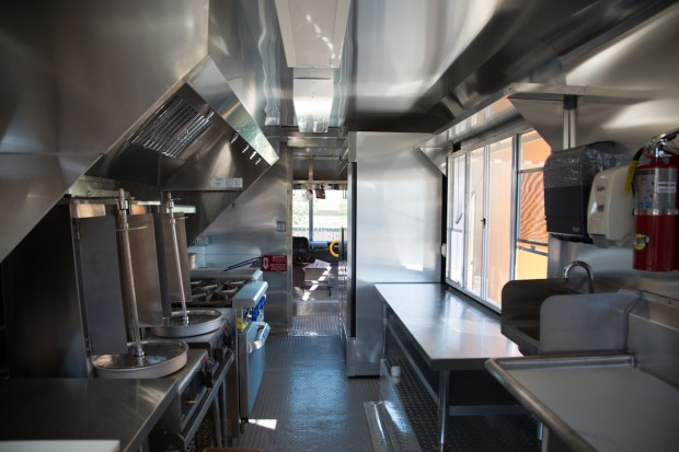 The interior of the Rue du Falafel truck features rotating vertical spits for cooking shawarma.