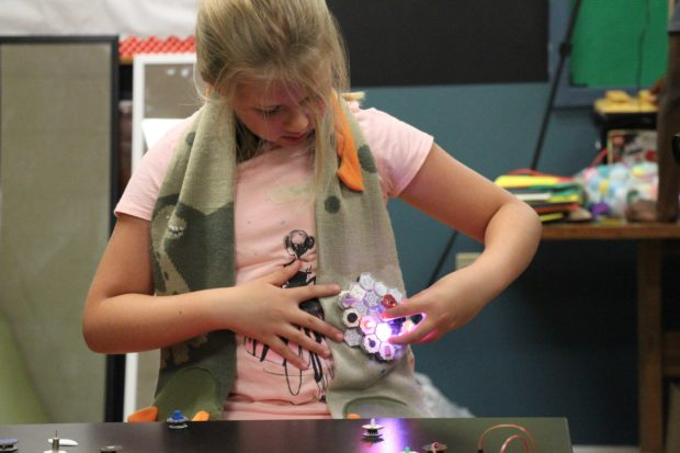 An 8-year-old girl making a motion reactive scarf
